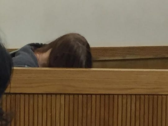 Angela Alexie keeps her head down as she is arraigned on murder and abuse charges in the death of her newborn baby whose body was found among waste at a recycling plant.