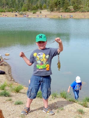 A scout from Ruidoso Troop 59 shows off his stringer of fish.
