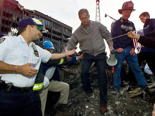 In this Sept. 14, 2001, file photo, Joseph Esposito, left, chief of department of the New York Police Department, offers help as President George W. Bush steps off of a pile of rubble after speaking at ground zero of the World Trade Center site in New York.