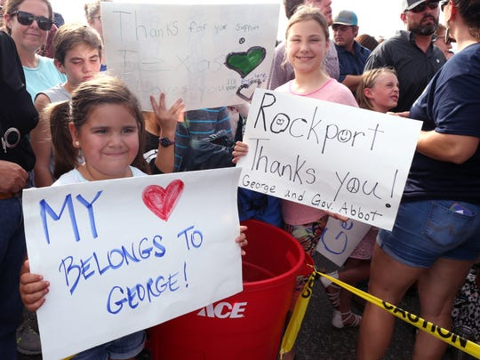 Audrey Hernandez (left), 6, and Bella Gilmore, 10, hold up signs they made for George Strait. Strait and Texas Governor Greg Abbott visited Rockport, TX and residents impacted by Hurricane Harvey on Thursday, September 21, 2017.
