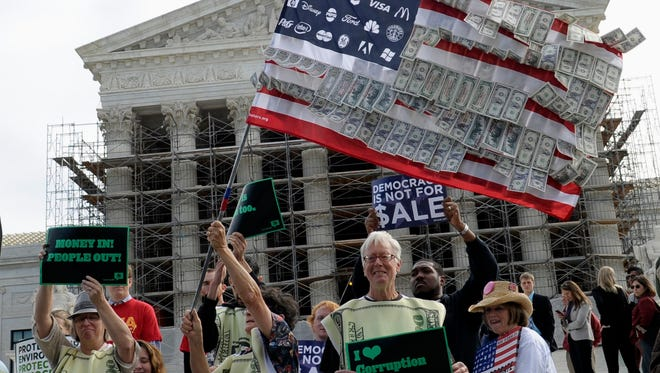 Demonstrators gather outside the Supreme Court in Washington, Tuesday, Oct. 8, 2013, as the court heard arguments on campaign finance.