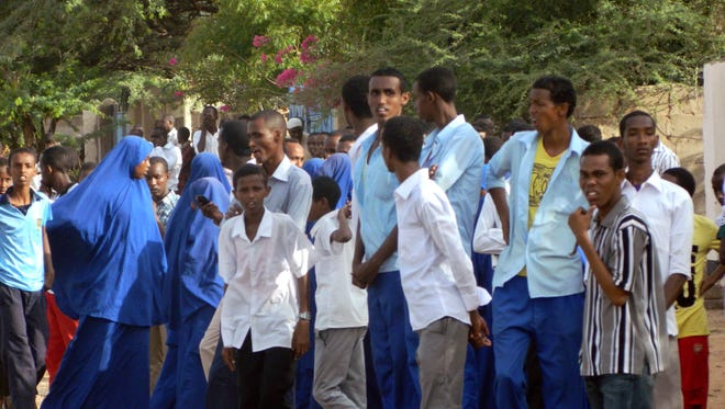 Students gather and watch outside Garissa University College on April 2, 2015.