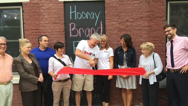 BrandFlick Founder David Wecker (center) celebrates the opening of his branding company during a ribbon cutting event on Friday.