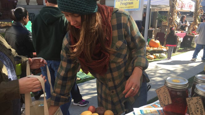 Karina French, farm assistant at Heartwood Farm, places potatoes into a customer's bag at the Burlington Farmers Market, seen on Oct. 3, 2015.