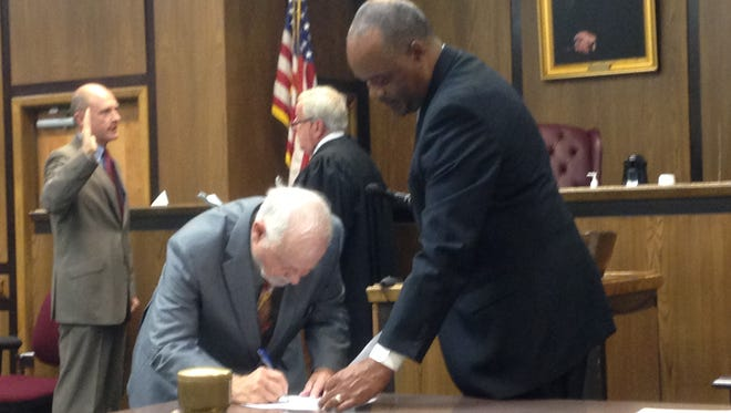 Accomack County Supervisor Paul E. J. Muhly signs a document after taking the oath of office as Accomack County Clerk of Court Samuel H. Cooper Jr. looks on, while Judge W. Revell Lewis III administers the oath to Supervisor Robert Crockett in Accomac, Virginia on Friday, Dec. 18, 2015.