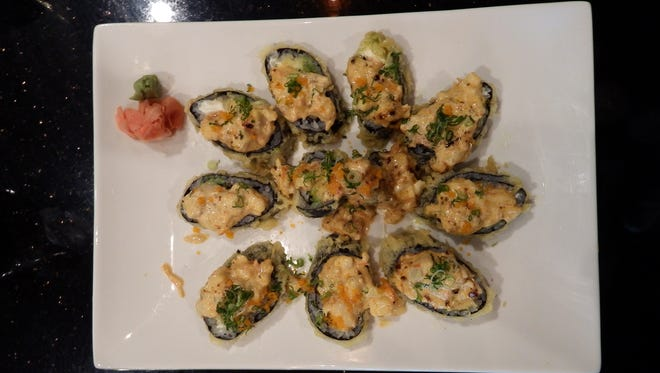 A super volcano roll, tempura roll with salmon, crab, eel, avocado and cheese topped with baked shrimp, squid, scallop and spicy mayo at Red Ginger at on May 11, 2016.