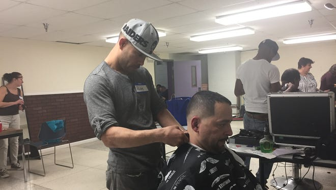 Ray Rosa, a barber with Laced Barber Lounge in Poughkeepsie, gives Ricardo Roman, 49, a homeless man, a haircut during the Point-in-Time count at the Family Partnership Health Center in the City of Poughkeepsie Monday afternoon.