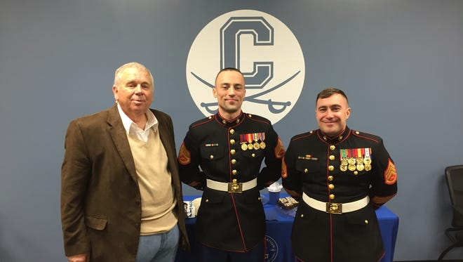 Chillicothe head football coach Ron Hinton stands with two Marines during a ceremony in which Hinton was honored with the Semper Fi Coach Award.