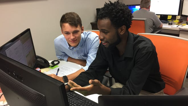Fuzic employee Deven Bridges, right, shows intern and Hamilton Southeastern High School student Nick Bisesi, left, what to do during a customer relations phone call. Bisesi interned at the Fishers startup for seven weeks during  the summer.