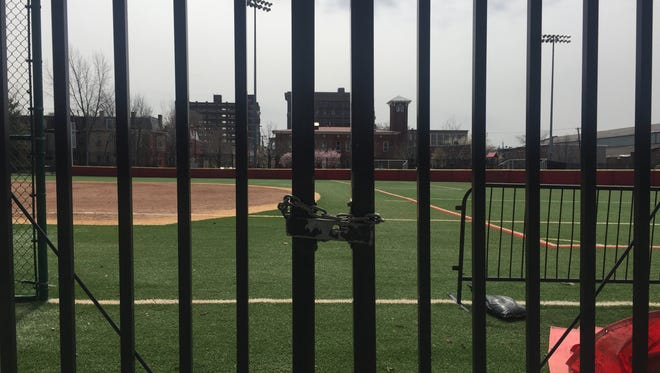 A locked gate surrounds athletic fields at Rutgers-Camden.