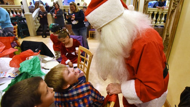 Ayden Baker and Chevy Johnson talk with Santa during a luncheon for kids with special needs at Adornetto's in Zanesville on Tuesday. Fourty children from Zanesville City Schools got pizza and presents courtesy the Noon Rotary.