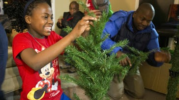Mirriam Nkulwe, 12, helps her father put up a Christmas tree Wednesday, Dec. 7, 2016, at their apartment. The Congolese family is celebrating its first Christmas and winter in the United States.