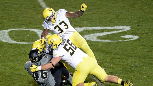 Oct 3, 2015; Boulder, CO, USA; Oregon Ducks linebacker Tyson Coleman (33) and defensive lineman Alex Balducci (56) and linebacker Rodney Hardrick (48) tackle Colorado Buffaloes running back Christian Powell (46) in the first quarter at Folsom Field. Mandatory Credit: Ron Chenoy-USA TODAY Sports