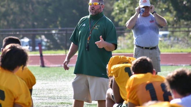 Rock Bridge head football coach Van Vanatta talks to his team at a social distance after its first official practice Monday at Sells Field.