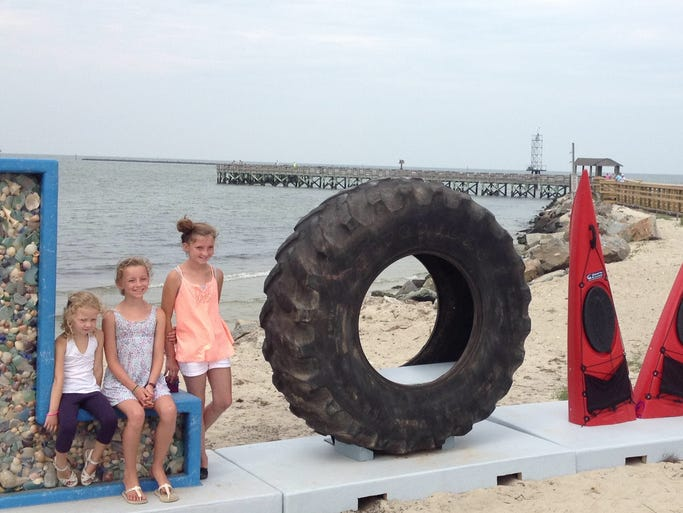 """Neiley (left), Veronica (middle), and Jayne Guinan pose for their mother Mia (not pictured) at the  town's recently-installed """"LOVEwork."""""""