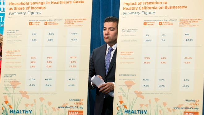 State Sen. Ricardo Lara, D-Bell Gardens, stands between a pair of charts outlining estimated cost savings concerning his single-payer health care bill at a Capitol news conference on Wednesday in Sacramento.