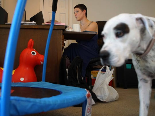 Family dog Lula walks by Isobel's toys and Erica Griffiths' workspace. Griffiths, who was diagnosed with stage IV breast cancer over a year ago, works full-time from home.