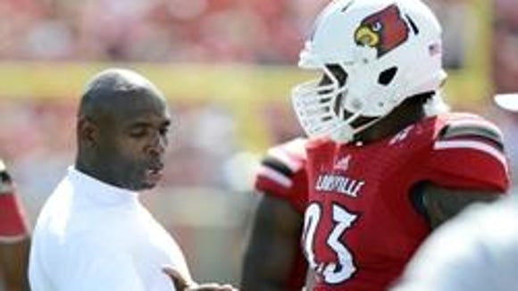 Louisville's Roy Philon talks with coach Charlie Strong.