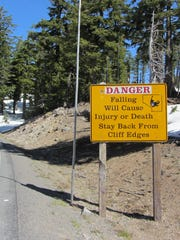 A sign makes clear the danger of falling down the cliffs that surround Crater Lake