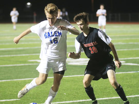 Salem's Michael Schroeder (No. 16) tries to elude defensive pressure from Livonia Churchill's Noah Anson (No. 18) during Tuesday night's district matchup.
