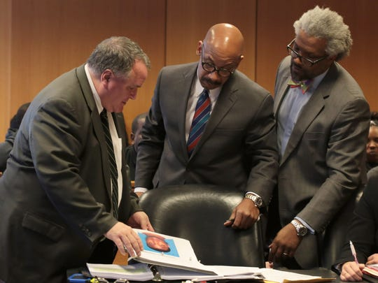 L-R Assistant Wayne County Prosecutor showing exhibit photos to defense attorneys, Marlon Blake Evans and Todd Perkins during preliminary examination for two men Dietrick Odums and Ottis Davis accused of killing rapper Dex Osama AKA(Byron Cox) at Frank Murphy Hall of Justice in Detroit on Friday, Oct. 23, 2015.