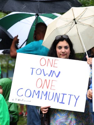In this Oct. 2 file photo, Mona Haleem, of Pittsford, holds a sign at the family unity walk in Pittsford to combat racism after a white supremacist flier was found in five Pittsford neighborhoods.