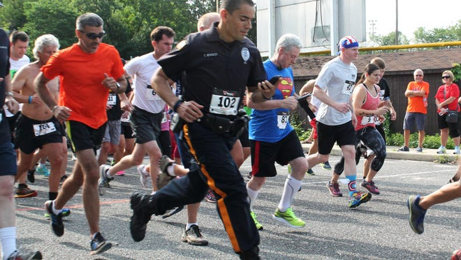 "Millville police Officer Manny Morales runs the 5k in full uniform and gear each year. ""It started as a challenge from other departments, but I do it to honor Chris and show our dedication."""