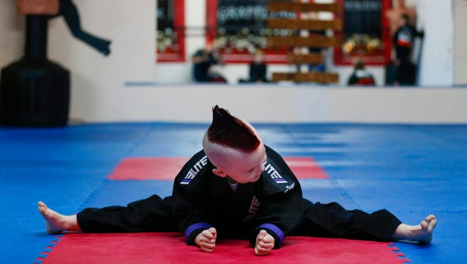 Six-year-old Lucas Glover does the splits as he practices his taekwondo forms at G + G Martial Arts in Fordland on Monday, Nov. 27, 2017.