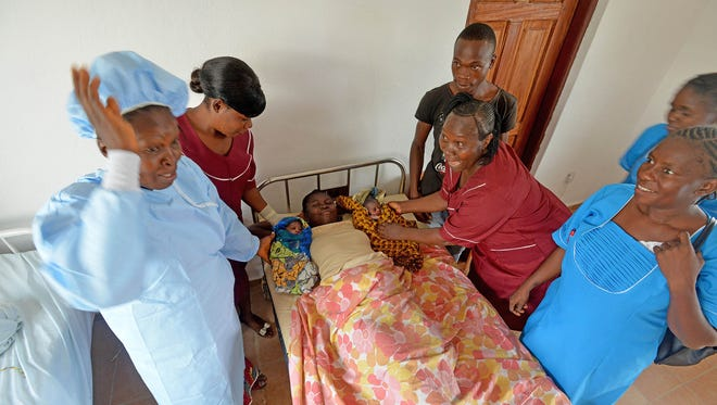 A team of traditional birth attendants and nurses rejoice after delivering the first baby in the newly opened Wellbody Alliance delivery center in Gbense Chiefdom in Sierra Leone on April 1, 2015. Salome Kamara delivered one of her twins at home; the second was breech and delivered at the center.