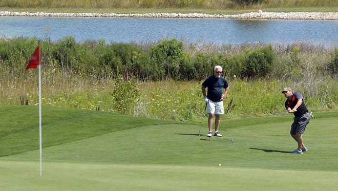 Golfers chip onto the green on Aug. 12 on hole No. 16 at The Orchards at Egg Harbor.