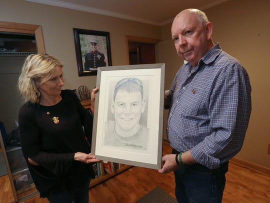 Rosemarie and Owen Lennon with a drawing of their son, Owen Jr., at their Pomona home Dec. 7, 2017. Marine Sgt. Owen Lennon Jr., died in an air crash in Mississippi this summer.