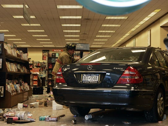 Rescue workers look over car inside the Barnes and Nobles store at 111 South Central Avenue in Hartsdale Oct. 13, 2006. The car went from the parking lot into the store injuring the driver and one store employee. (Frank Becerra Jr./The Journal News)