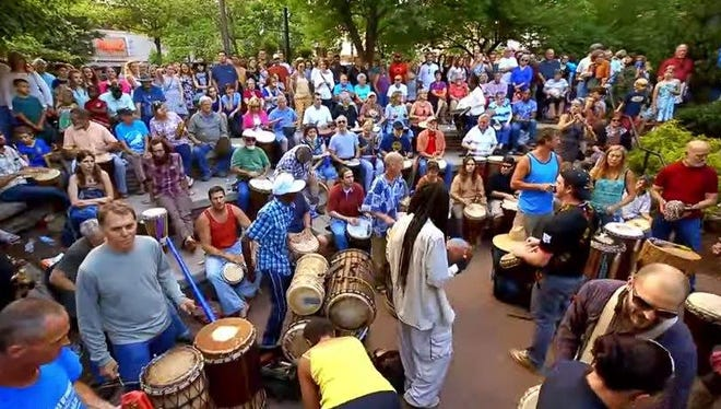 Still image from an Asheville branding campaign video, which shows the weekly downtown drum circle in Pritchard Park.