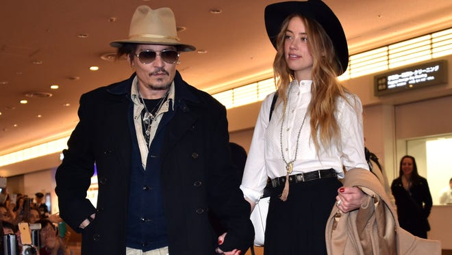 """Johnny Depp accompanied by his fiancee, Amber Heard, arrives at Tokyo International Airport on Jan. 26, 2015, for the Japan premiere of his latest movie """"Mortdecai."""""""