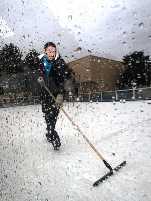 Larry Martinez, a facilities manager with the city of Farmington's Parks, Recreation and Cultural Affairs department, removes rainwater from the ice rink on Thursday at the Farmington Civic Center.