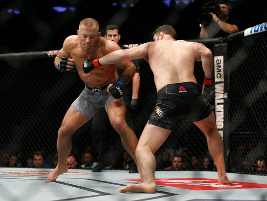 Georges St-Pierre (blue gloves) fights Michael Bisping