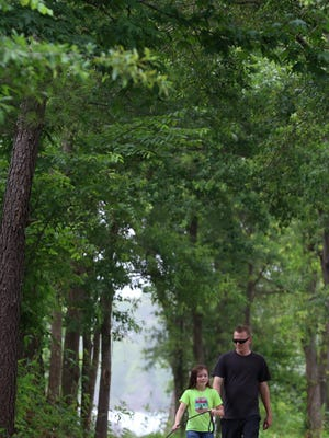 "Eight-year-old Kayleigh Thurber walks ""Rosa"" with her dad, Ryan Thurber, along the newly opened Catawba Riverfront Greenway trail Saturday afternoon, June 27, 2020, at Tuckaseegee Park in Mount Holly."