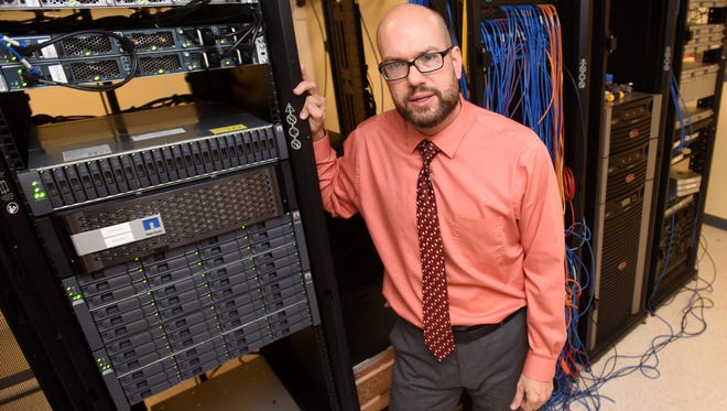 Charles Thacker, executive director of technology for the Farmington Municipal School District, poses with some of the district's servers on Wednesday at the Career and Technology Education Center in Farmington.