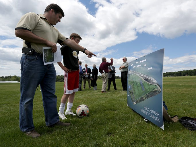 Chuck Keefe, president of the MC United Soccer Club and his son Ryan Keefe, 11, both of Wausau, and a member of the MC United Galacticos soccer team look at an artist's rendering of the Marathon County Field Sports Complex as CN (Canadian National Railway Company) donated $25,000, Wednesday, July 16, 2014, to plant trees at the complex next to the Wausau Curling Center.