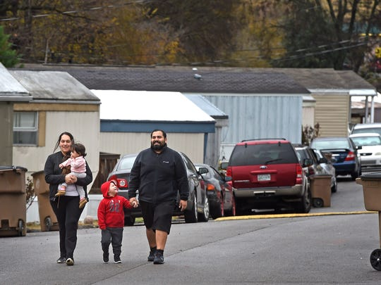 Cesar Melchor and wife Maria Gomez take a walk around the Shady Hills mobile park neighborhood with two of their children, Jacob and Natalia.
