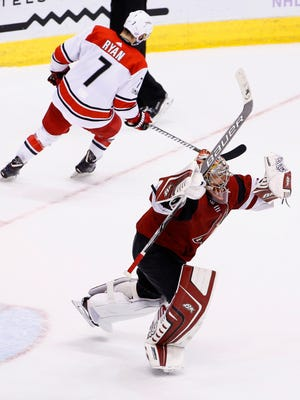 Arizona Coyotes goalie Antti Raanta, right, celebrates after making a save on a shot by Carolina Hurricanes center Derek Ryan (7) during a shootout of an NHL hockey game Saturday, Nov. 4, 2017, in Glendale, Ariz. The Coyotes defeated the Hurricanes 2-1. (AP Photo/Ross D. Franklin)