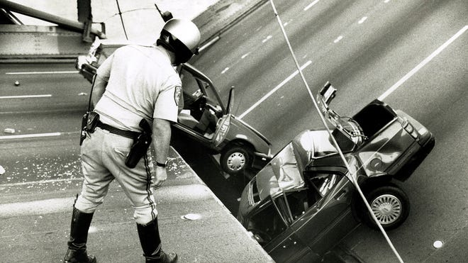 In this photo taken Oct. 17, 1989, a California Highway Patrol Officer checks the damage to cars that fell when the upper deck of the Bay Bridge collapsed onto the lower deck  after the Loma Prieta earthquake in San Francisco.