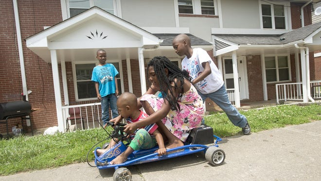 From left: Zaylon Flyth, 6, King Flyth, 2, Janita Rhodes, 10, and Zarious Flyth, 6, play on a go-kart at Hillcrest Apartments on Friday. Programs at the housing community as well as others in Asheville are encouraging residents to improve their communities.