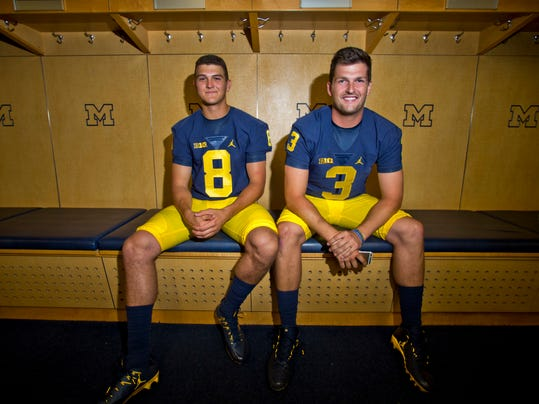 FILE - This Aug. 7, 2016 file photo shows Michigan quarterbacks John O'Korn (8) and Wilton Speight (3) sitting for a photo in the locker room during the NCAA college football team's preseason media day at Michigan Stadium in Ann Arbor, Mich. It's game week for Michigan, and coach Jim Harbaugh is playing games of another kind — keeping his roster secret. He also won't say whether returning starter Wilton Speight or seldom-used senior John O'Korn will take the first snap for the 11th-ranked Wolverines against No. 17 Florida in Texas in the opener for both schools. (AP Photo/Tony Ding, file)