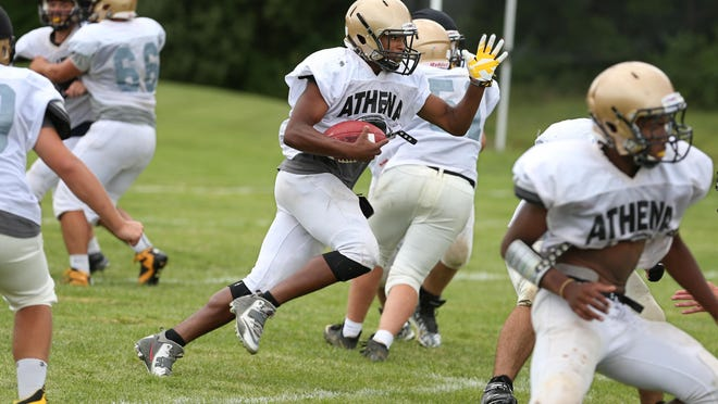 Athena quarterback Tavon Granison explodes through a hole in the defense for yardage during practice at Greece Athena High School in Greece on Tuesday. Athena is the ninth stop on the Democrat & Chronicle's high school football camp tour.