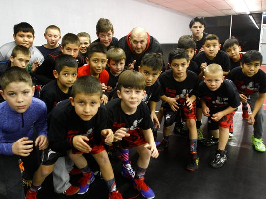 Members of the Stout Wrestling Academy and Levi Stout pose for a portrait Wednesday in Farmington.