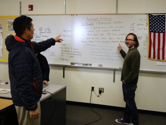 Rocinante High School Principal Peter Deswood, left, and teacher Nate Thompson discuss some of the elements of the school's redesign plan on Wednesday.