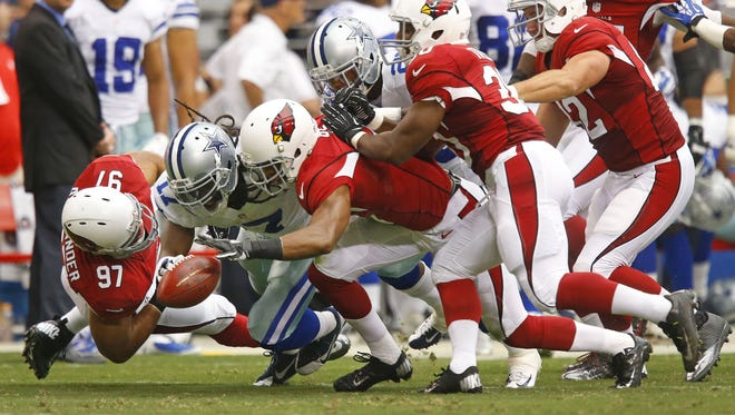Arizona Cardinals' Lorenzo Alexander and Justin Bethel cause a fumble by Dallas Cowboys' Dwayne Harris in the first half of their NFL game  Saturday, Aug. 17, 2013 in Glendale. The Cardinals recovered.