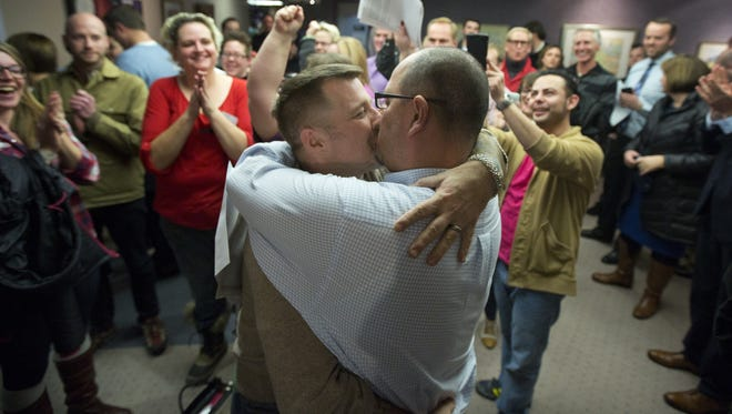 Chris Serrano, left, and Clifton Webb kiss after being married, as people wait in line to get licenses outside of the marriage division of the Salt Lake County Clerk's Office in Salt Lake City on Dec. 20, 2013.