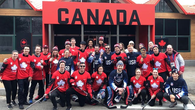 Athletes and officials from the Canadian and U.S. Olympic teams commemorate their ball hockey showdown on Friday at the Winter Olympics.
